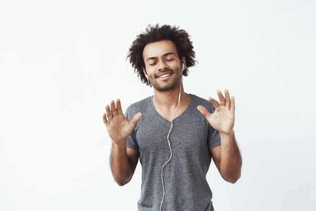 Homem africano alegre ouvindo música em fones de ouvido, dançando cantando.
