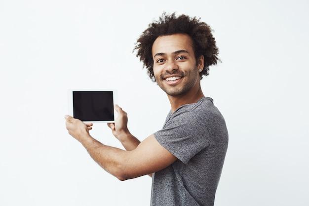 Homem africano alegre que sorri mostrando a tela vazia da tabuleta sobre a parede branca.