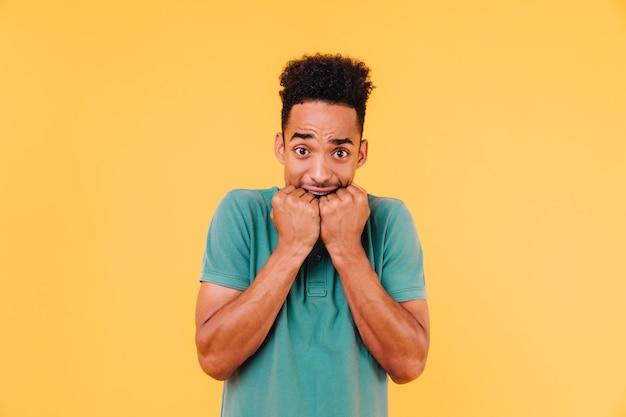 Homem africano assustado posando. cara negro preocupado em pé de camiseta verde brilhante.