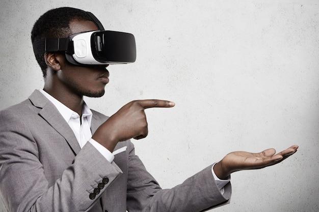 Homem africano atraente com roupa formal e óculos 3d, apontando os dedos para o espaço da cópia acima da palma da mão aberta, como se estivesse usando algum gadget.