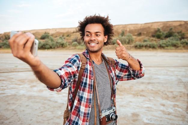Homem africano atraente sorridente tirando uma selfie com o celular e mostrando os polegares para cima