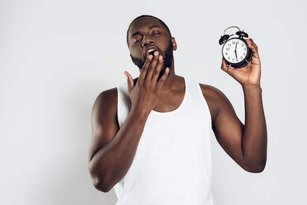 Homem africano boceja segurando o despertador.