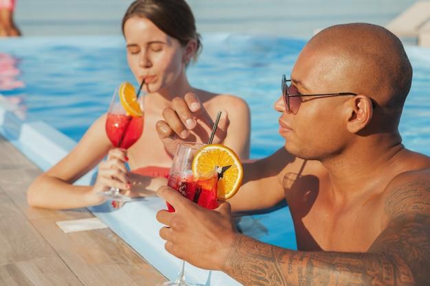 Homem africano bonito e sua linda namorada desfrutar de cocktails na piscina do hotel resort. casal feliz bebendo à beira da piscina. amor, conceito de romance