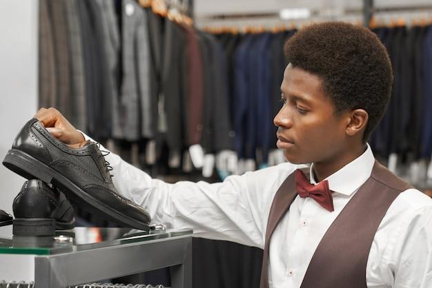 Homem africano bonito escolhendo sapatos pretos na loja.