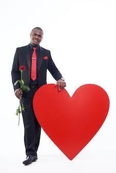 Homem africano bonito vestindo na suíte preta e gravata vermelha, inclinando-se de grande coração vermelho decorado.