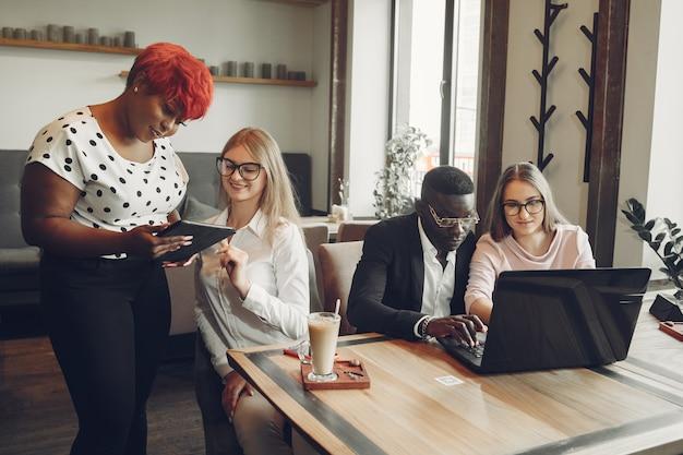 Homem africano. cara de terno preto. alunos com um laptop. menina de blusa branca.