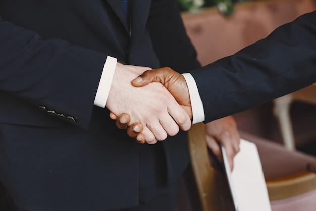 Homem africano. cara de terno preto. pessoas misturadas apertam as mãos.