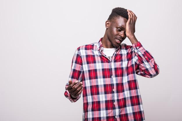 Homem africano chateado e triste agarrando sua testa com a mão em pé, perdendo o prazo de inscrição da loteria de diversidade ou esquecendo de desligar a eletricidade em casa.