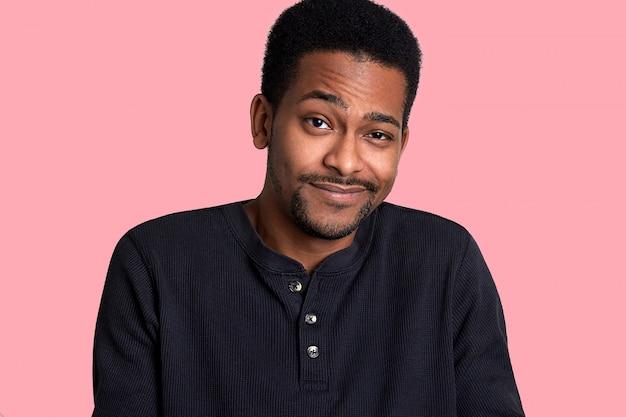 Homem africano com barba e bigode tripula seus olhos e sorrisos, masculino parece tímido. modelo fica isolado no blackground rosa. cara jovem veste camisa preta. conceito de pessoas.