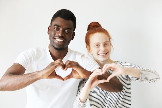 Homem africano com camiseta branca e mulher caucasiana ruiva com top listrado