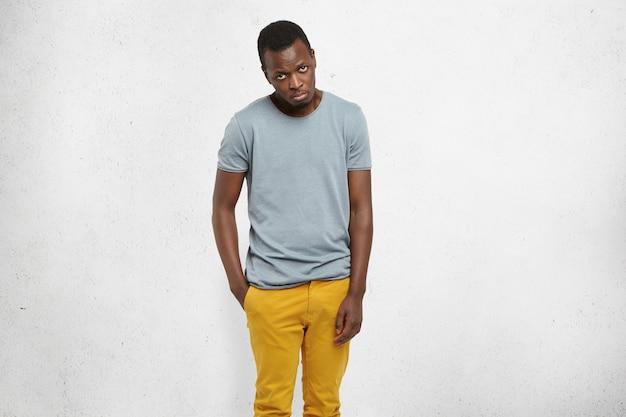 Homem africano com camiseta casual e calça mostarda, olhando para a câmera com expressão culpada