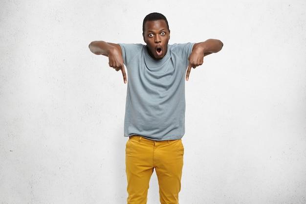 Homem africano com camiseta e calça mostarda apontando o dedo para baixo e olhando surpreso