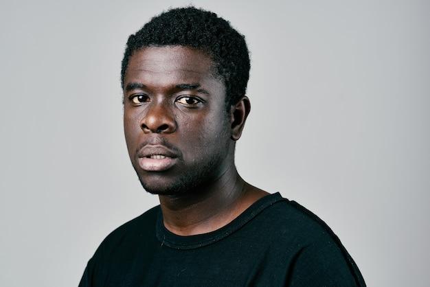 Homem africano com camiseta preta posando de estúdio de moda