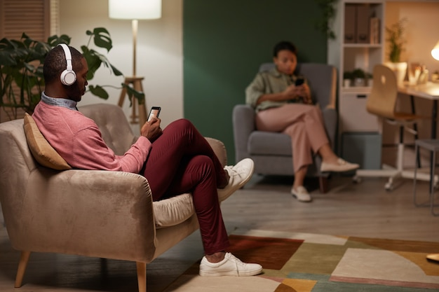 Homem africano com fones de ouvido sem fio, sentado no sofá e usando seu telefone celular para ouvir música com uma mulher usando seu telefone ao fundo