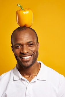 Homem africano com pimenta de sino amarelo sobre a cabeça que smilling.