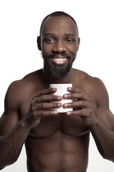 Homem africano com uma xícara branca de chá ou café, isolado no estúdio branco.