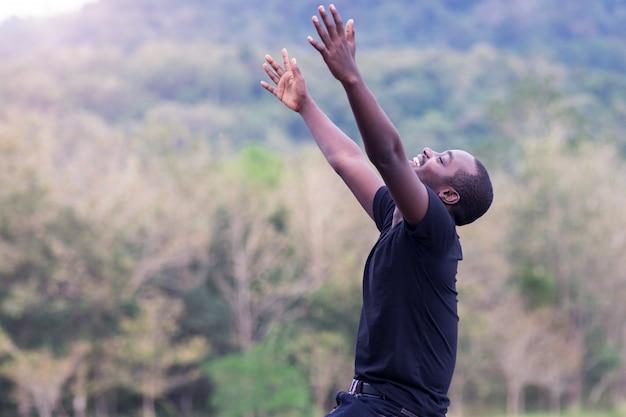 Homem africano da liberdade que aprecia e relaxa com no fundo natural verde.