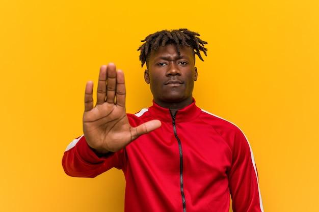 Homem africano de aptidão jovem em pé com a mão estendida, mostrando o sinal de stop, impedindo você.