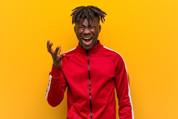 Homem africano de aptidão jovem gritando de raiva