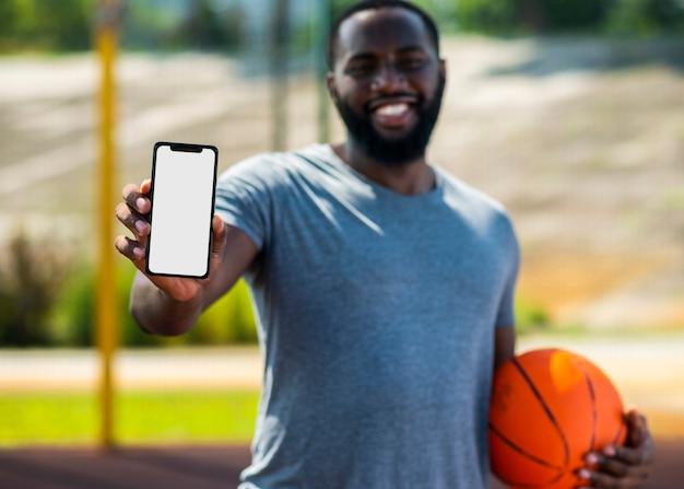 Homem africano de basquete, mostrando o seu telefone