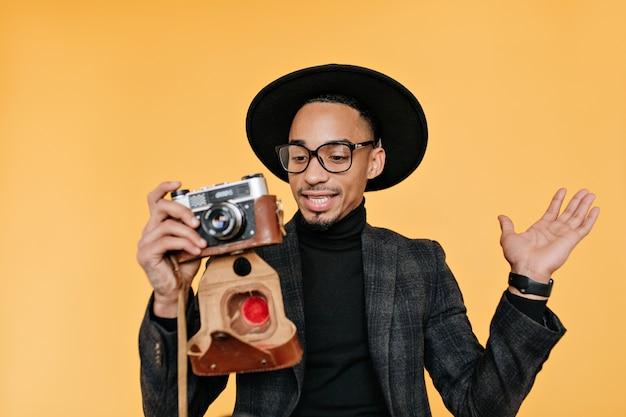 Homem africano de chapéu e terno segurando a câmera e expressando espanto. retrato de negro despreocupado posando na parede amarela durante a sessão de fotos.