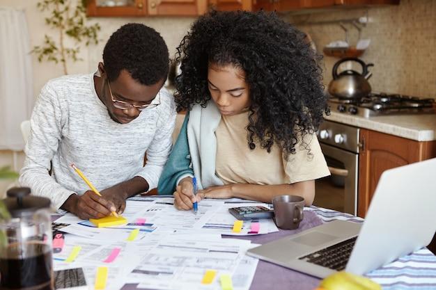 Homem africano de óculos e mulher com cabelo encaracolado tendo olhares concentrados enquanto está ocupado trabalhando com contas não pagas