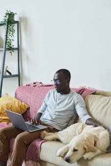Homem africano de óculos, sentado no sofá com o cachorro e trabalhando online em casa