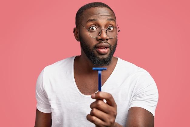 Homem africano de pele escura e barbudo segurando e anunciando rasor
