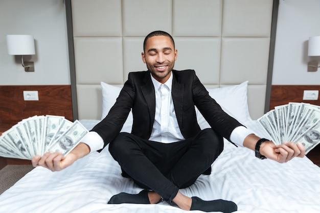 Homem africano de terno medita com dinheiro nas mãos e olhos fechados na cama em um quarto de hotel