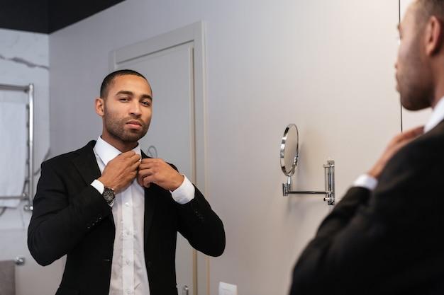 Homem africano de terno olhando para o espelho e a camisa dos botões no quarto do hotel