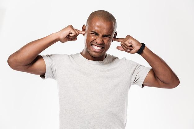 Homem africano descontente fecha os ouvidos de um barulho.