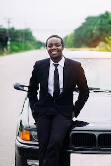 Homem africano do negócio que está na frente de seu carro.