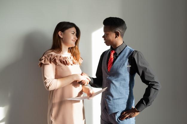 Homem africano e mulher caucasiana apertando as mãos no escritório