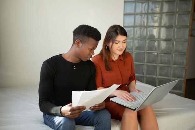 Homem africano e mulher caucasiana trabalhando em casa com um laptop