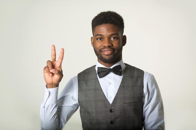Homem africano elegante em um colete em uma parede branca com um gesto de mão