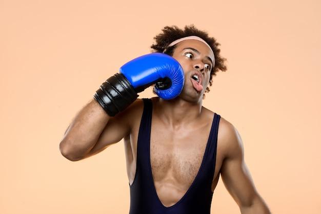 Homem africano em luvas de boxe, batendo-se