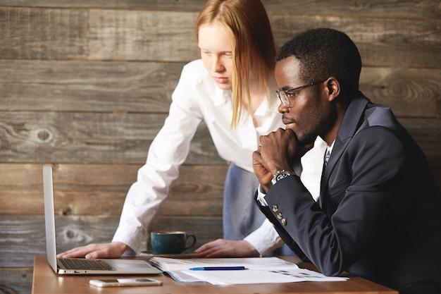Homem africano em terno formal e mulher caucasiana em camisa branca, videoconferência e negociação
