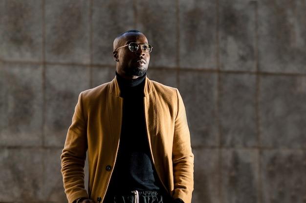 Homem africano em um terno elegante e elegante, andando em uma cidade metropolitana, olhando de lado.