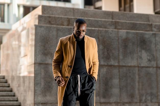 Homem africano em um terno elegante e elegante, andando por uma cidade metropolitana.