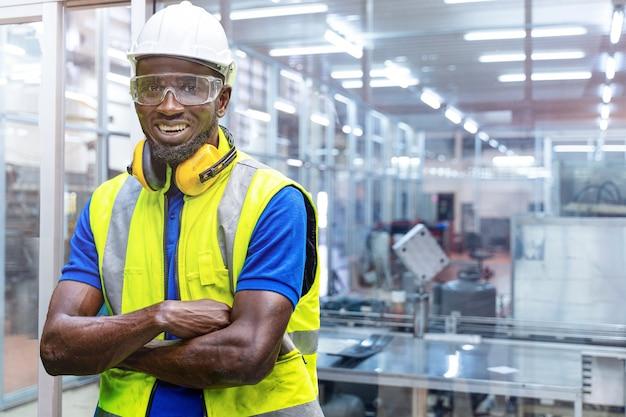 Homem africano, engenheiro de fábrica, confiante com vestido verde de trabalho e capacete de segurança