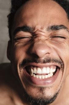 Homem africano engraçado isolado sobre o cinza. olhos fechados.