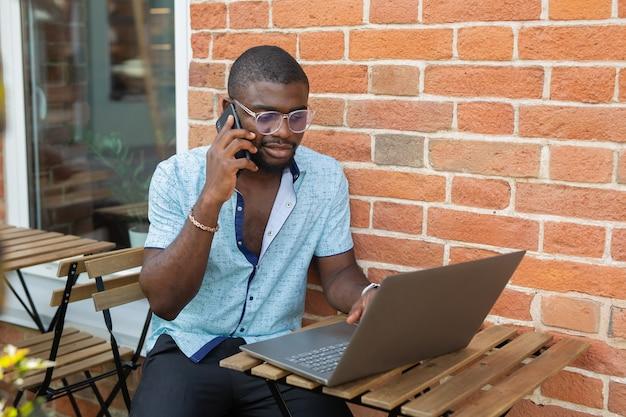 Homem africano falando no celular com o laptop no fundo da parede de tijolos
