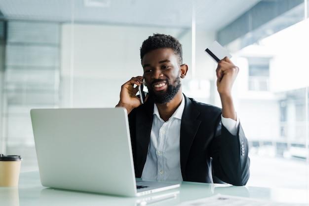 Homem africano falando no telefone e lendo o número do cartão de crédito enquanto está sentado no escritório