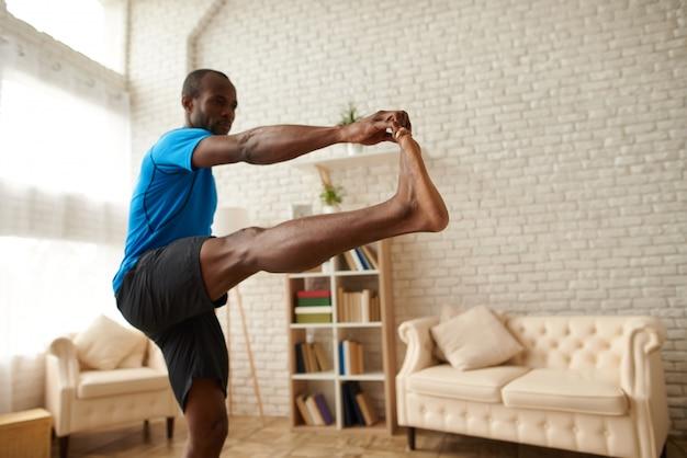 Homem africano fazendo exercícios de alongamento para os músculos das pernas.