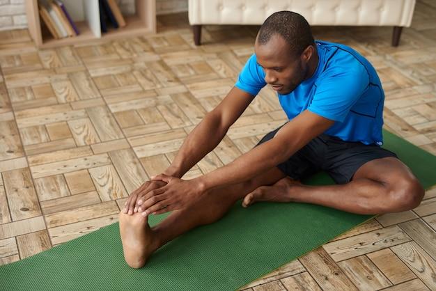 Homem africano fazendo exercícios de alongamento para os músculos de pernas.