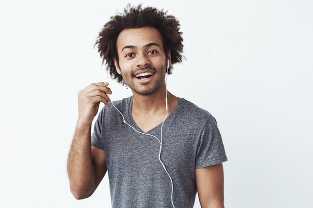 Homem africano feliz apagando sorrindo de fone de ouvido.