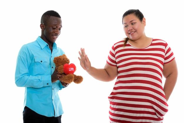 Homem africano feliz dando ursinho de pelúcia para uma mulher asiática gorda