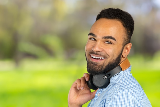 Homem africano feliz que sorri escutando a música nos auscultadores. fundo branco