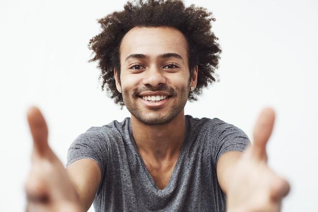 Homem africano feliz sorrindo esticando as mãos para a câmera.