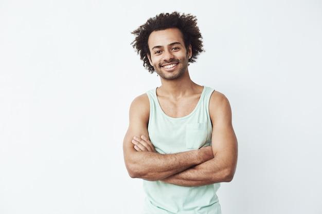 Homem africano feliz sorrindo posando com braços cruzados.